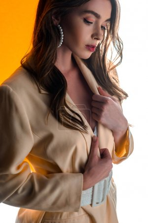 attractive young woman touching blazer on orange and white