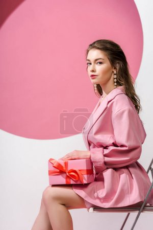 attractive girl holding gift box while sitting on white and pink