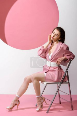 Photo for Stylish woman in blazer with belt sitting on chair on white and pink - Royalty Free Image