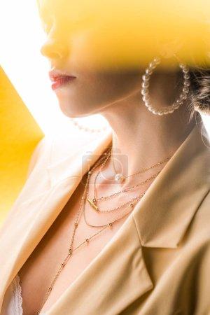 Photo pour Vue recadrée de jeune femme en collier et boucles d'oreilles sur orange et blanc - image libre de droit