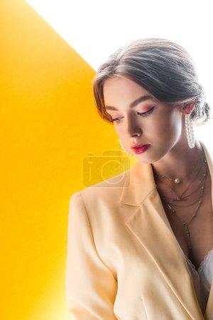 Photo pour Belle jeune femme en collier et boucles d'oreilles sur orange et blanc - image libre de droit