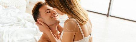 Photo pour Photo panoramique de petite amie embrassant et embrassant copain en appartement - image libre de droit