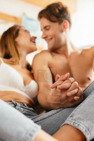 selective focus of smiling boyfriend and girlfriend in bra holding hands in apartment