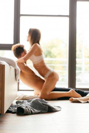selective focus of girlfriend in underwear and boyfriend hugging on floor in apartment