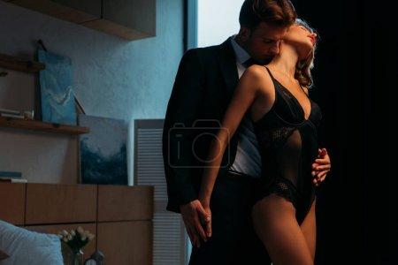 Photo pour Homme d'affaires embrassant et embrassant amie sexy en costume noir - image libre de droit