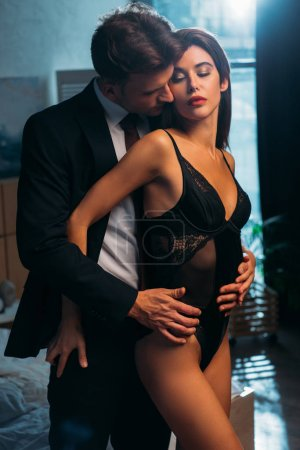 Photo for Businessman hugging and kissing attractive girlfriend in bodysuit in apartment - Royalty Free Image