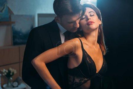 Photo pour Homme d'affaires étreignant et embrassant jolie petite amie en body dans l'appartement - image libre de droit
