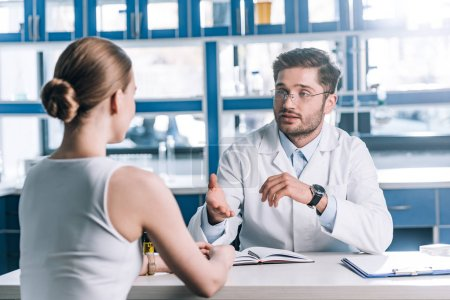Photo for Selective focus of handsome doctor in glasses looking at patient and gesturing in clinic - Royalty Free Image