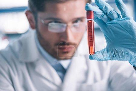 Photo pour Foyer sélectif de l'immunologiste barbu tenant le tube à essai avec le liquide rouge - image libre de droit