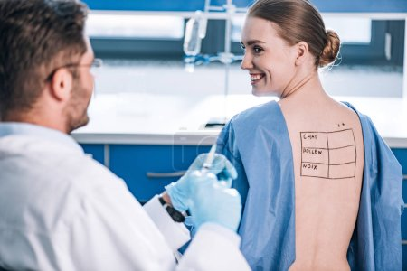 selective focus of happy patient with letters on marked back looking at allergist