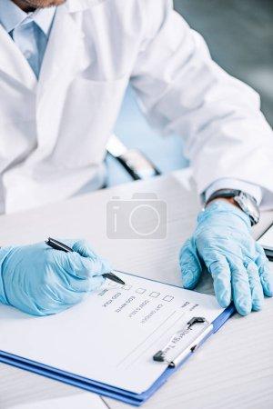 Photo pour Vue recadrée de l'immunologiste tenant un stylo près du presse-papiers - image libre de droit