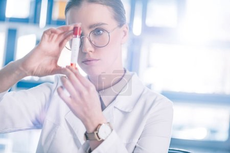 Photo pour Selective focus of beautiful immunologist in glasses holding test tube - image libre de droit