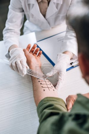 Photo for Overhead of allergist in latex gloves holding ruler near marked hand on man in clinic - Royalty Free Image