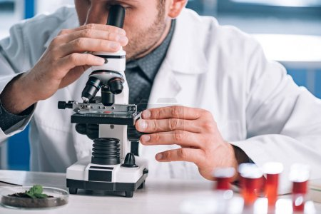 Photo for Cropped view of bearded biochemist looking through microscope in laboratory - Royalty Free Image
