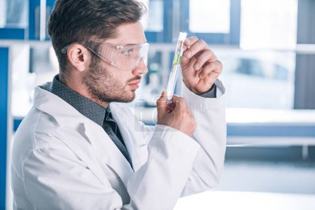 Photo for Handsome man in goggles and white coat holding test tube with green plant in laboratory - Royalty Free Image