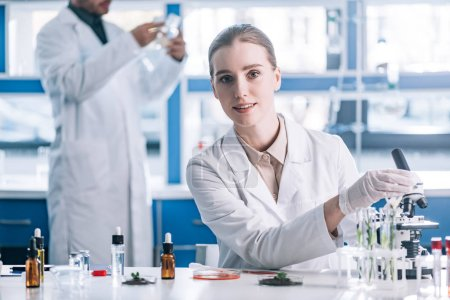 Photo for Selective focus of happy and attractive biochemist near microscope and plants in test tubes - Royalty Free Image
