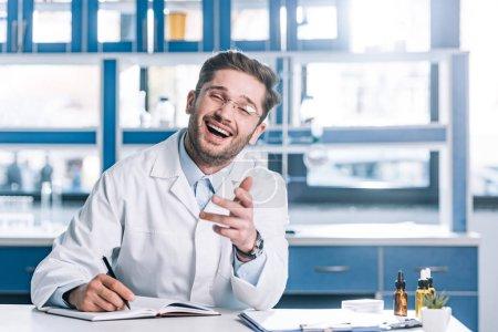 Photo pour Docteur gai en lunettes et en manteau blanc assis au bureau et en gestation dans la clinique - image libre de droit