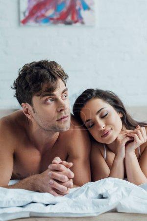 Photo pour Bel homme rêveur regardant loin tandis que belle copine penchée sur son épaule - image libre de droit