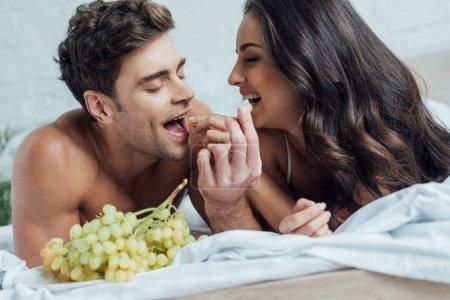 Photo pour Heureux jeune couple se nourrissant mutuellement avec des raisins tout en étant couché sur le lit - image libre de droit