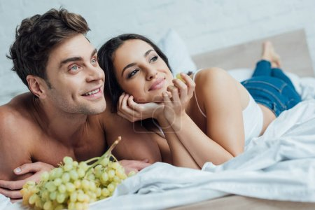 Photo for Happy young couple looking away while lying on bed near bunch of grapes - Royalty Free Image