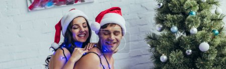 Photo for Panoramic shot of happy couple covered with christmas garland and wearing santa hats - Royalty Free Image