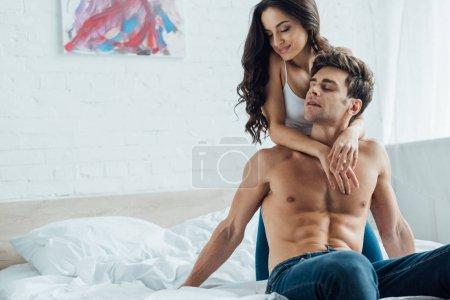 Photo pour Heureux jeune femme étreignant sexy torse nu petit ami dans chambre - image libre de droit