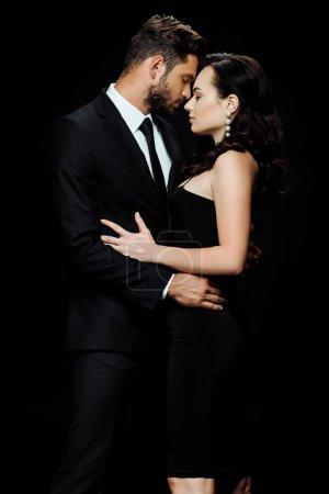Photo pour Vue latérale de bel homme barbu avec les yeux fermés debout avec une jolie fille isolée sur noir - image libre de droit