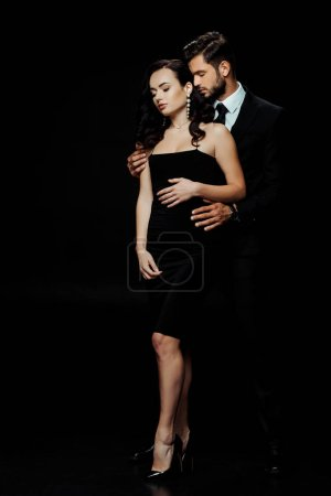 Photo for Handsome bearded man with closed eyes hugging attractive girl isolated on black - Royalty Free Image