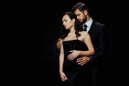 Photo for Handsome bearded man with closed eyes hugging attractive girlfriend isolated on black - Royalty Free Image