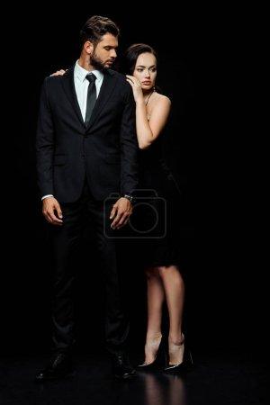 Photo pour Attrayant femme en robe stand près de barbu homme sur noir - image libre de droit