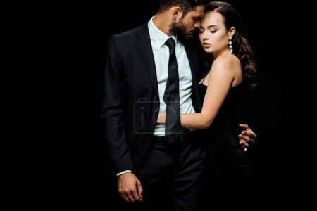 Photo for Attractive woman in dress hugging handsome man isolated on black - Royalty Free Image