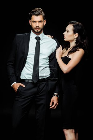 attractive girl in dress undressing boyfriend in suit standing with hand in pocket isolated on black