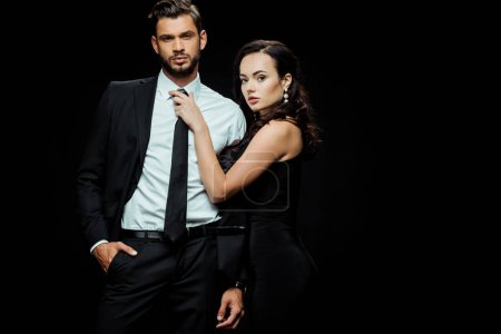 Photo for Attractive girl in dress touching tie of boyfriend in suit standing with hand in pocket isolated on black - Royalty Free Image