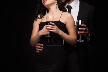 Photo for Cropped view of man and woman holding glasses with red wine isolated on black - Royalty Free Image