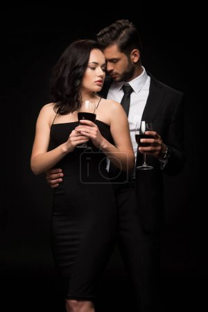 Photo for Bearded man and attractive girl holding glasses with red wine isolated on black - Royalty Free Image
