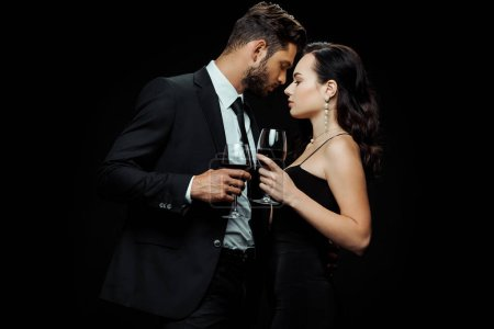 Photo for Side view of handsome man and attractive woman holding glasses with red wine isolated on black - Royalty Free Image