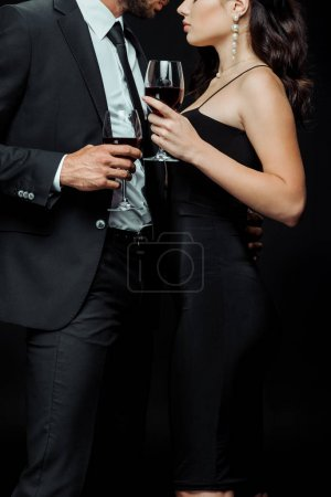 cropped view of man hugging woman holding glass of red wine isolated on black