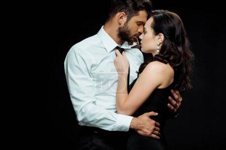 Photo pour Vue latérale de la femme attrayante avec les yeux fermés touchant cravate de l'homme en costume isolé sur noir - image libre de droit