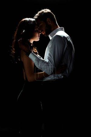 Photo pour Vue latérale de l'homme heureux touchant femme tout en se tenant isolé sur noir - image libre de droit