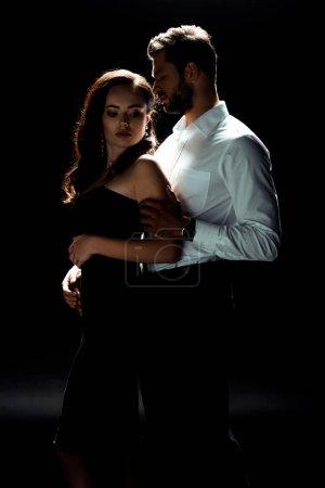 Photo pour Homme barbu debout avec femme en robe sur noir - image libre de droit