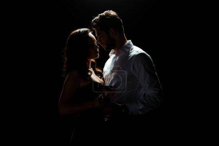 Photo pour Bel homme debout avec femme tenant un verre de vin rouge isolé sur noir - image libre de droit