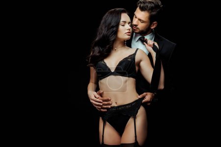 Photo pour Attractive woman in sexy lingerie touching tie of man isolated on black - image libre de droit