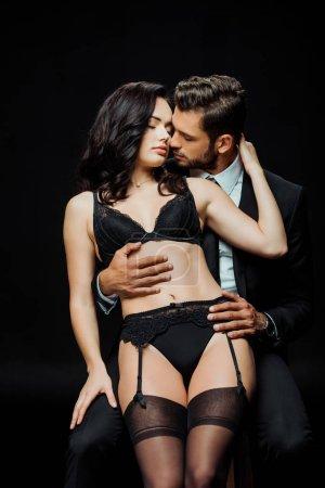Photo pour Un homme passionné touche une séduisante femme en sous-vêtements isolée sur un noir - image libre de droit