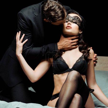 Photo pour Homme touchant le cou d'une femme sexy en sous-vêtements et lacet bandeau isolé sur noir - image libre de droit