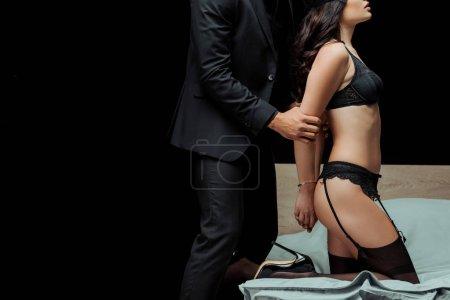 Photo pour Crochet vue d'un homme touchant une séduisante femme en sous-vêtements sexy isolée sur noir - image libre de droit