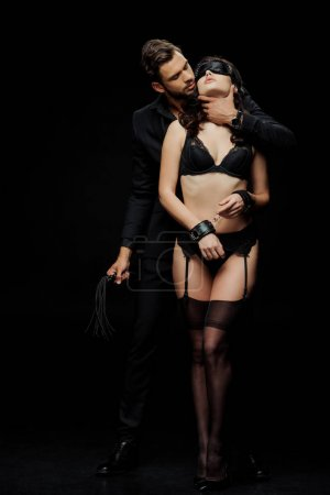 Photo pour Femme soumise en sous-vêtements, les yeux bandés et les menottes en cuir près de l'homme avec fouet fouet isolé sur noir - image libre de droit