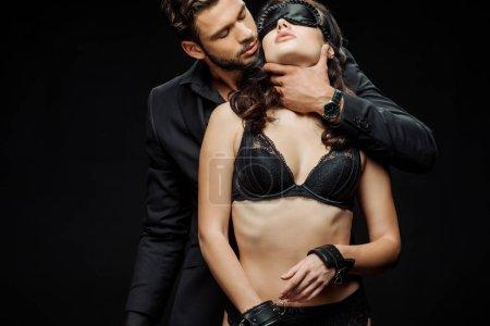Photo pour Femme soumise en sous-vêtements et les yeux bandés près de l'homme avec fouet fouet isolé sur noir - image libre de droit