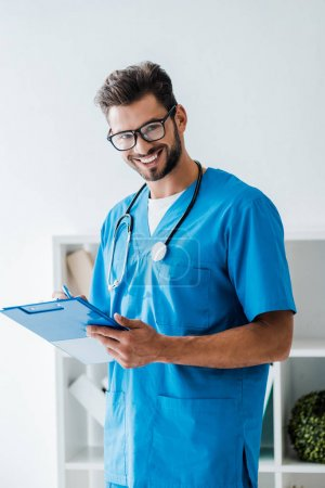 handsome veterinarian smiling at camera while writing prescription on clipboard