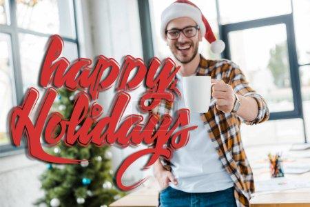 Photo pour Foyer sélectif de l'homme barbu heureux chapeau santa tenant tasse près de l'arbre de Noël dans le bureau avec illustration joyeuses fêtes - image libre de droit