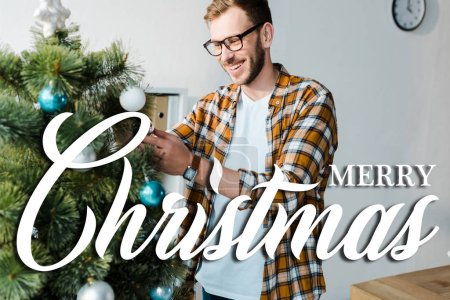 Photo for Happy bearded man in glasses decorating christmas tree in office with merry christmas illustration - Royalty Free Image